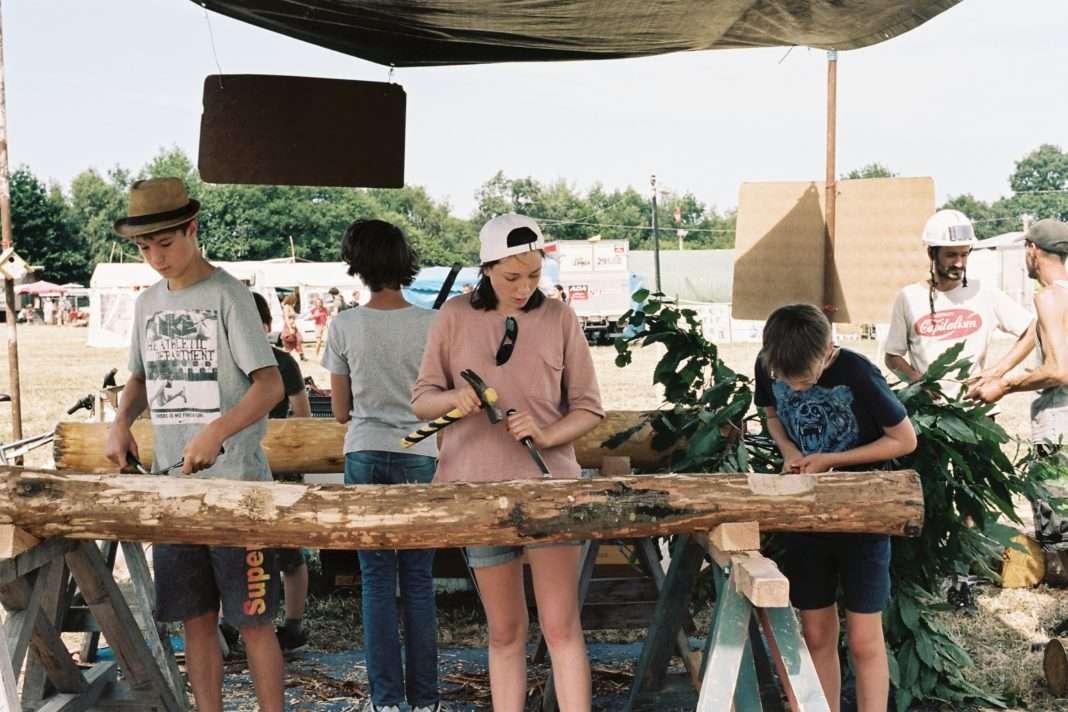 Une jeune femme travaille le bois à la ZAD de Notre-Dames-Des-Landes lors d'un weekend de construction collective à l'été 2019. Photographie : June Loper pour Radio Parleur