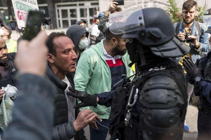 Un manifestant est tenu à distance par un policier