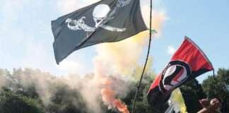 Avant de s'élancer hors du camp le samedi matin, les activistes en ont fait le tour, en formation, à grands renforts de chants et fumigènes. Les drapeaux anarchistes, écologistes et antifascistes ont flotté au-dessus du camp comme dans les cortèges toute la durée des événements. Photo Pierre-Olivier Chaput pour Radio Parleur.