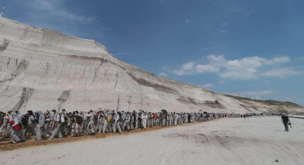 Les activistes d'Ende Gelände progressent dans le paysage désertique et abyssal de la mine de charbon. Ils se dirigent vers le bas de cette vallée artificielle en contournant les petits barrages sur leur route.