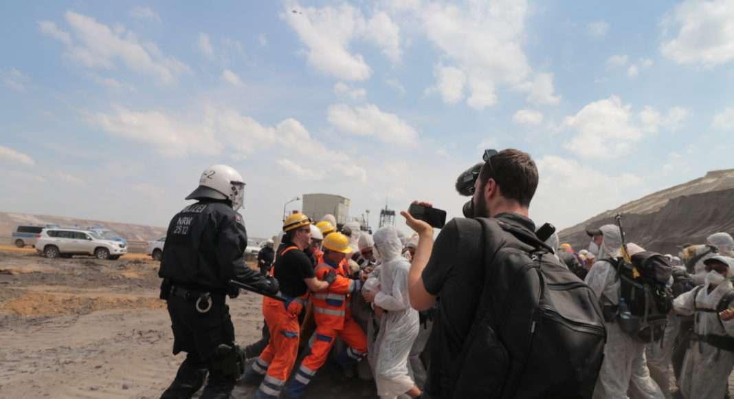 Les activistes sont stoppés alors qu'ils atteignent le niveau de l'excavatrice par un mélange de policiers et d'employés vếtus d'une tenue RWE, la compagnie qui possède la mine. La riposte est brutale, et plusieurs d'entre eux devront être soignés par les médecins qui suivent la manifestations.