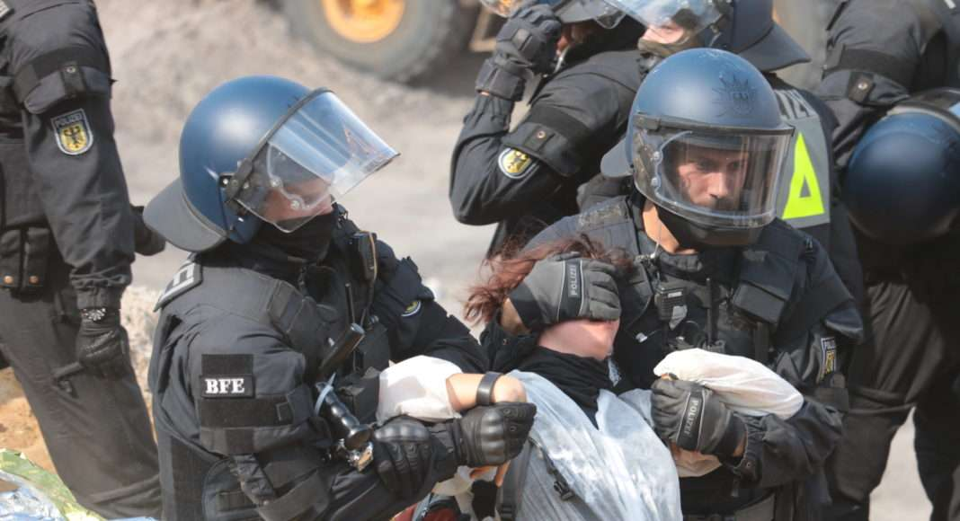 Après plusieurs heures en plein soleil, les policiers entament les arrestations. Celles et ceux qui ne suivent pas docilement se voient poussés, fortement maintenus au visage ou les poignets tordus pour les faire avancer.