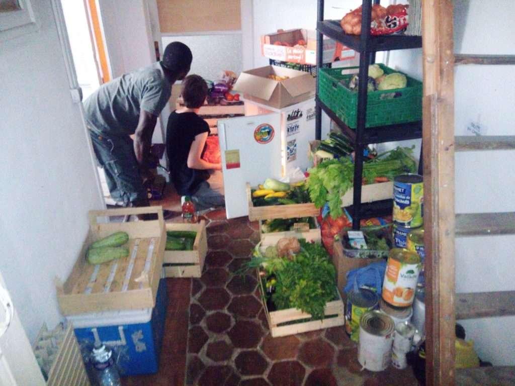 Deux personnes devant un stock de nourriture et frigo à l'Athénée Libertaire de Bordeaux acceuil de jour pour les expulsés des squats. Juillet 2019