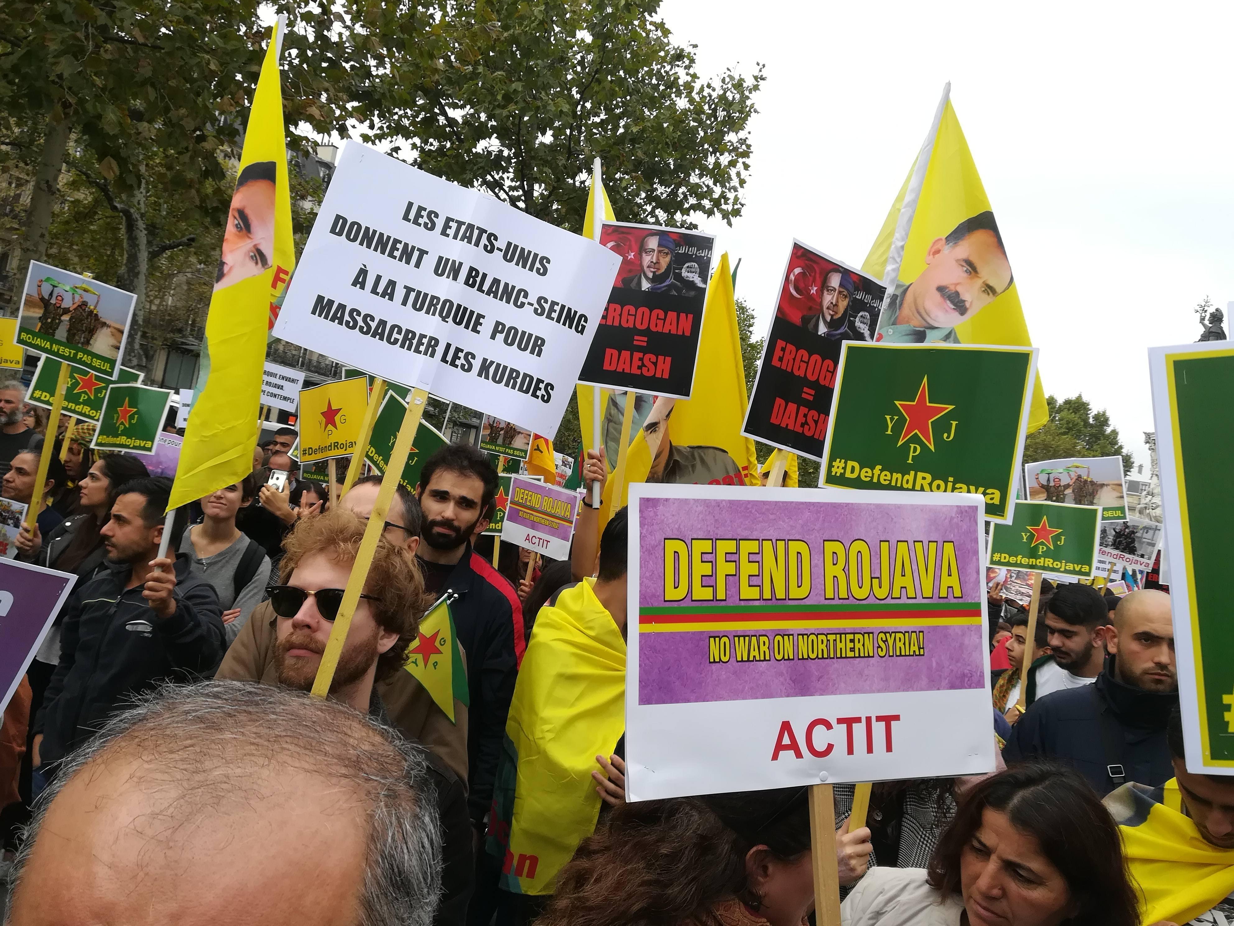 Les pancartes de soutien au Rojava côtoient celles qui dénonçent les agissements de Donald Trump et de Erdogan ( Photographie : Yoann Compagnon pour Radio Parleur)