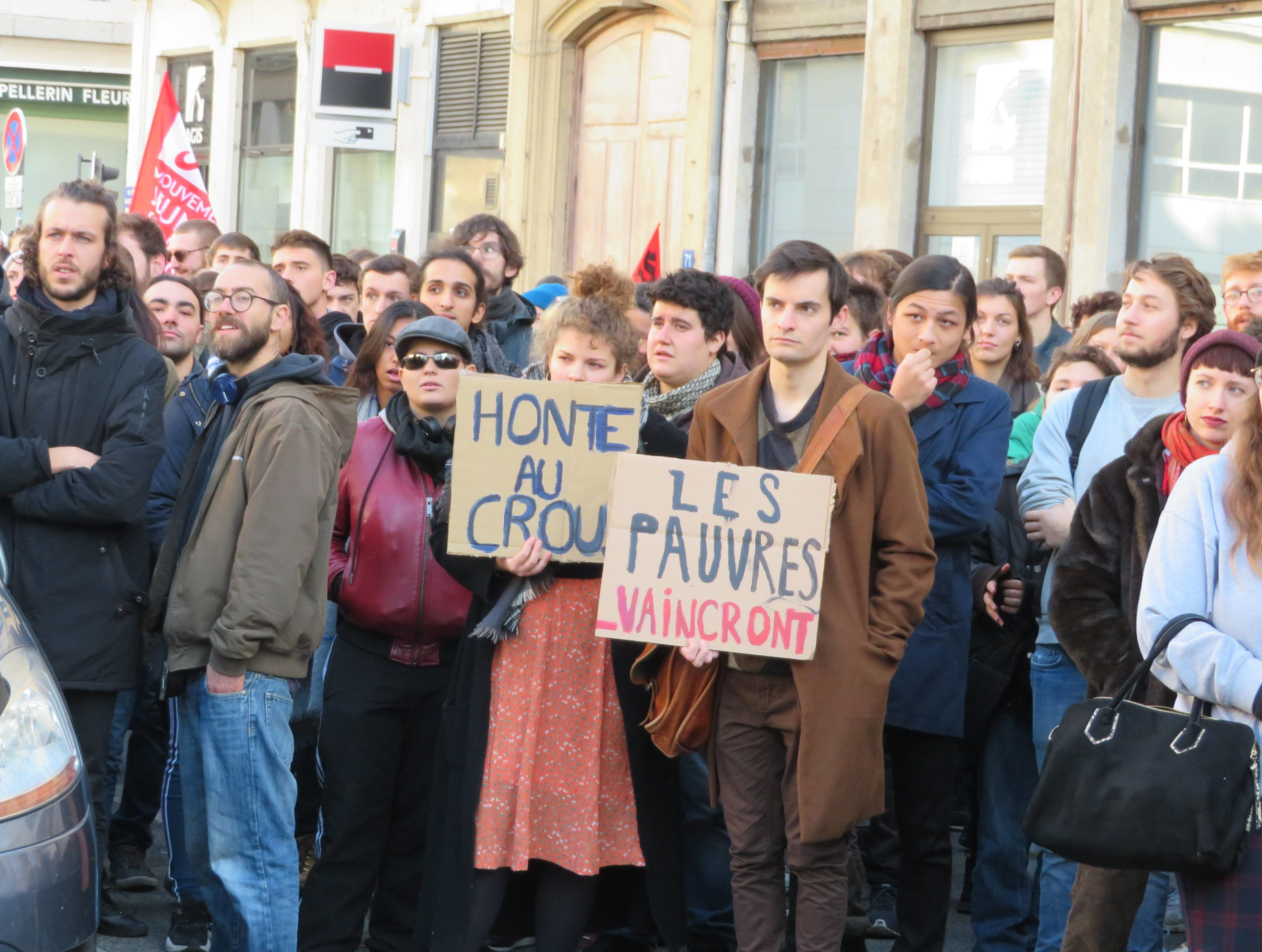 """Des personnes rassemblées, dont deux portant des pancartes indiquant : """"Honte au Crous"""" et """"Les pauvres vaincront"""""""