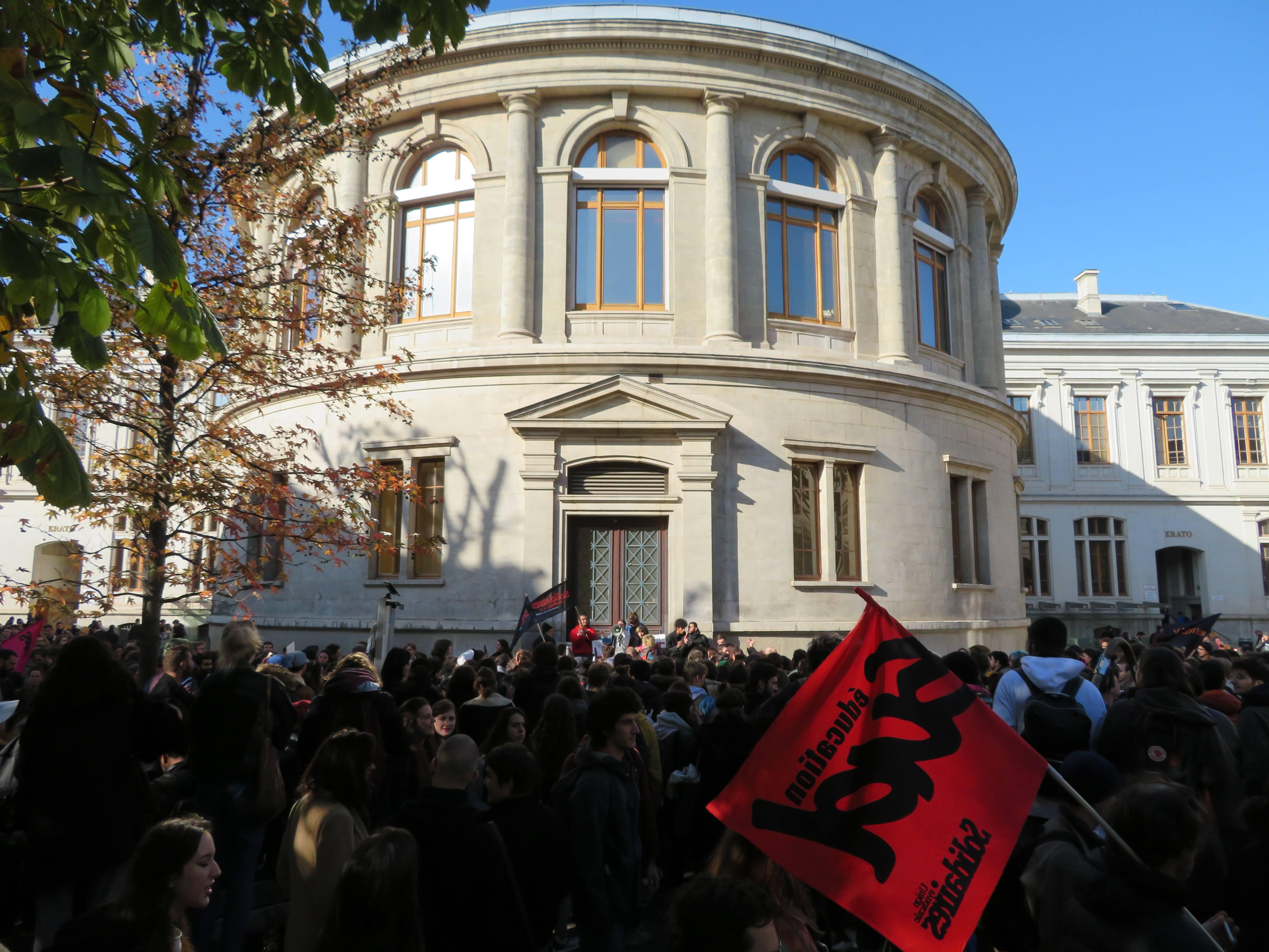 Manifestant.es rassemblé.es devant la façade du campus des Berges du Rhône de l'Université Lumière-Lyon-2
