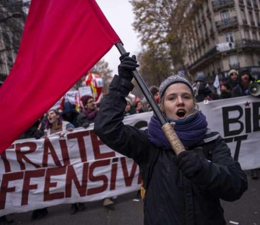 Manifestation 5 décembre grève générale, une femme brandit un drapeau rouge, symbole de la Commune de Paris