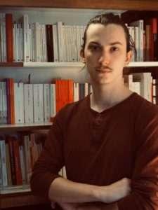 Portrait de Loïc Bonin à partir de la taille. Il se tient debout devant une bibliothèque.