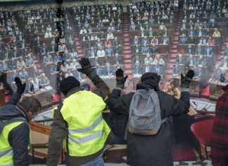 Le 8 février 2018, des Gilets Jaunes manifestent devant l'Assemblée Nationale à Paris. Frappant sur les panneaux de bois qui la protège, ils tentent d'interpeller leurs député.es et réclament une démocratie plus directe. Photo : Sylvain Lefeuvre pour Radio Parleur