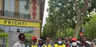 Des livreurs en lutte se tiennent devant un hub frichti