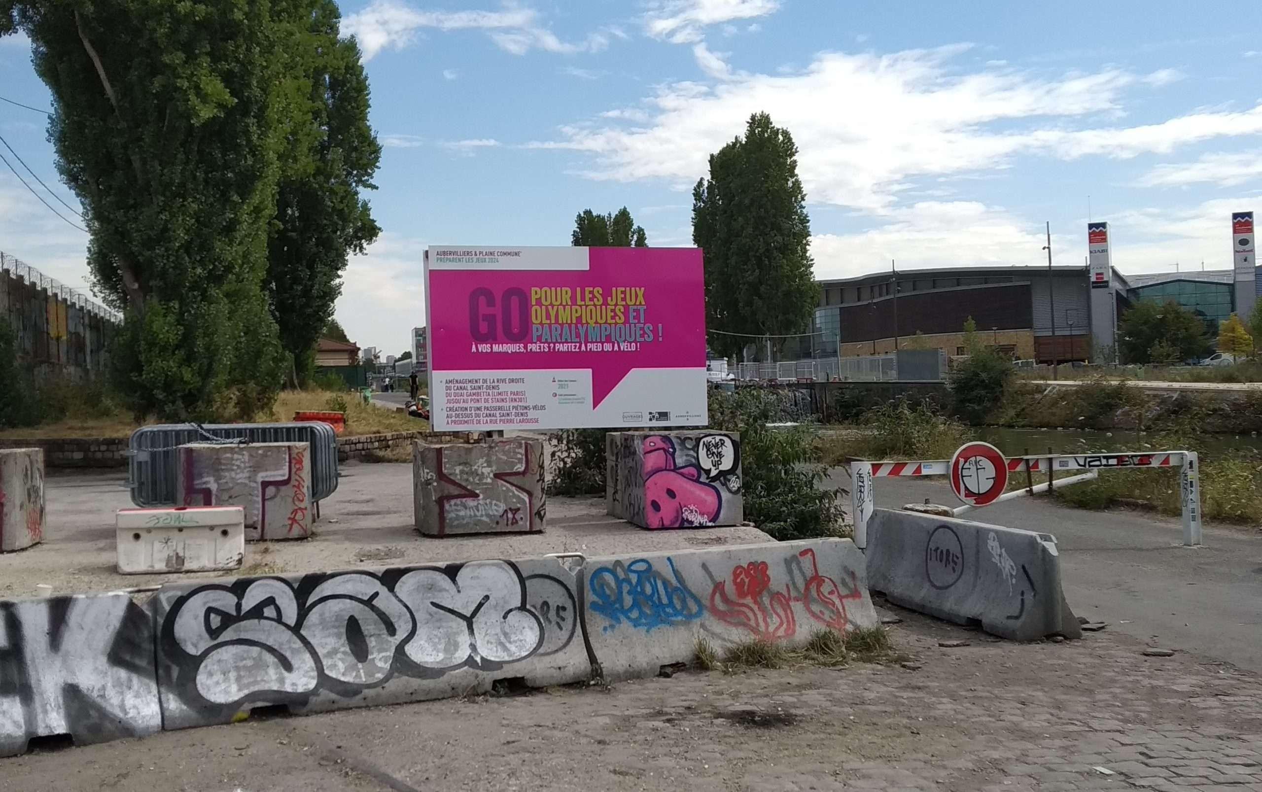 À quelques mètres du camp ,un panneau annonce les travaux prévus pour l'organisation des jeux olympiques 2024 à Saint-Denis. Photographie : Léonardo Carota pour Utopia 56.