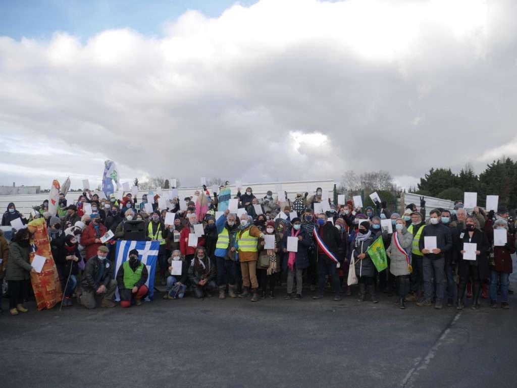 Les militants brandissent le serment du Triangle devant la palissade des travaux
